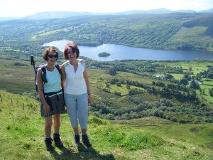Two walkers on a hilltop with Glenade Lake beneath